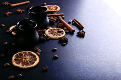 A cup of coffee, star anise, cinnamon, dried orange and coffee beans on a dark kitchen countertop. Fragrant spices for a drink, stock photography