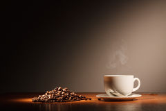Cup with coffee and steam. Coffee cup with steam and coffee beans stock images
