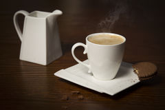 Cup of coffee with steam and cookie. Royalty Free Stock Images