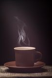 Cup of Coffee with Steam on wooden board. Black Background Stock Image