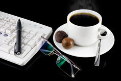 Cup of coffee-still-life. Cup of coffee, part of keyboard,glasses,pen on a black background royalty free stock photos