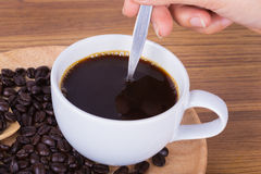 Cup of coffee stirred by hand Stock Images