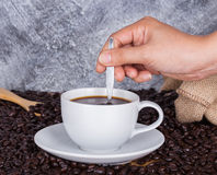 Cup of coffee stirred by hand Royalty Free Stock Image