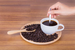 Cup of coffee stirred by hand Royalty Free Stock Photo