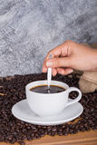 Cup of coffee stirred by hand Stock Photos
