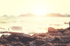 cup of coffee on the stone in the beach royalty free stock image