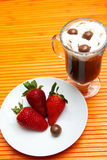 Cup of coffee with strawberries. Cup of coffee with cream and three strawberries on a saucer. Focus is on the strawberries royalty free stock photos