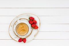 Cup of coffee and strawberries on white wooden table. Top view Stock Photo