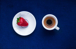 Cup of coffee and a strawberry. On deep blue background royalty free illustration