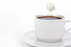 Cup of coffee with sugar. White cup of coffee with falling sugar royalty free stock images