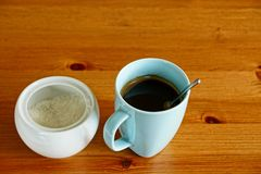 A cup of coffee and a sugar bowl with sugar on a wooden table Stock Photography