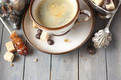 Cup of coffee, sugar cubes and chocolate drops on old wooden background with copy space Stock Images