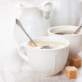 Cup of coffee with sugar cubs and milk jug Stock Photography