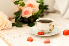 Cup of coffee, sugar hearts and a bouquet of cream roses Stock Image