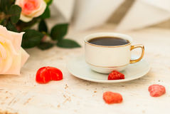 Cup of coffee, sugar hearts and a bouquet of cream roses Stock Images