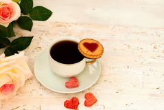 Cup of coffee, sugar hearts and a bouquet of cream roses Royalty Free Stock Image