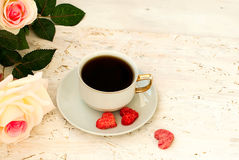 Cup of coffee, sugar hearts and a bouquet of cream roses Royalty Free Stock Photo