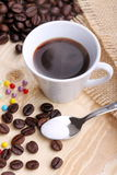 Cup of coffee and sugar pearls. Cup of coffee with sugar pearls and coffee grains on wooden fir Stock Photos