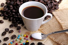 Cup of coffee and sugar pearls. Cup of coffee on wood with sugar pearls and jute cloth Royalty Free Stock Photography