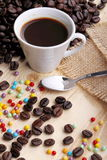 Cup of coffee and sugar pearls. Cup of coffee on wood with sugar pearls and jute cloth Royalty Free Stock Image