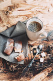 A Cup of coffee ,sugars and metal spoon, biscuits sprinkled with sugar on a napkin on a wooden table.  Royalty Free Stock Images