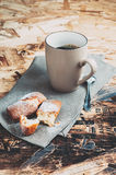 A Cup of coffee ,sugars and metal spoon, biscuits sprinkled with sugar on a napkin. On a wooden table Royalty Free Stock Image
