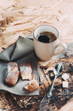 A Cup of coffee ,sugars and metal spoon, biscuits sprinkled with sugar on a napkin. On a wooden table Royalty Free Stock Photography