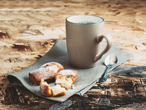 A Cup of coffee ,sugars and metal spoon, biscuits sprinkled with sugar on a napkin. On a wooden table Stock Photo