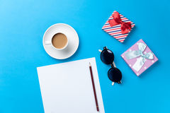 Cup of coffee with sunglasses, gift and paper Royalty Free Stock Images