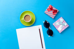 Cup of coffee with sunglasses, gift and paper Stock Image