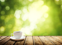 Cup coffee and sunny trees. Background Royalty Free Stock Photo