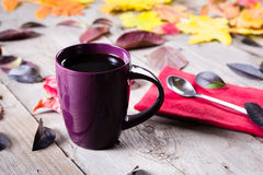 Cup of coffee surounded by red, purple and yellow fall leaves. Cup of coffee surounded by red and purple fall leaves. Top view royalty free stock photos