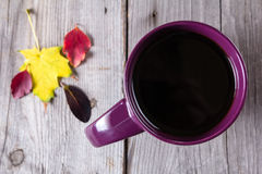 Cup of coffee surounded by red, purple and yellow fall leaves. Cup of coffee surounded by red and purple fall leaves. Top view stock photo