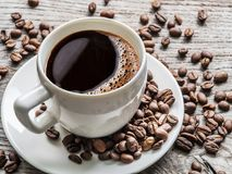 Cup of coffee surrounded by coffee beans. Top view. stock images