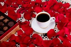 Cup of coffee surrounded by red rose petals sitting next to a box of chocolate. White porcelain cup and saucer trimmed with told filled with coffee sitting on a royalty free stock photography