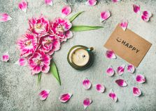 Cup of coffee surrounded with tulip flowers and sign happy. Spring morning concept. Flat-lay of cup of coffee surrounded with pink tulip flowers, petals and sign Royalty Free Stock Image
