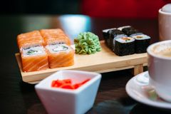 Cup coffee and sushi on table royalty free stock photo
