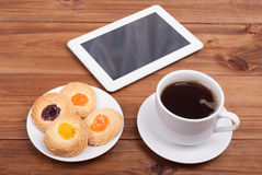 Cup of coffee and sweet cakes digital tablet Stock Photography