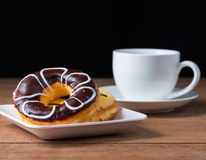 A cup of coffee with  sweet chocolate donut. On wooden Stock Image