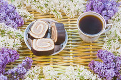 Cup of coffee, sweet dessert and blossoming lilac Stock Photo