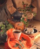 Cup of coffee, sweets and grains of coffee on a wooden table royalty free stock photography