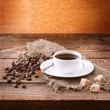 Cup of coffee, sweets and roasted beans. Coffee concept. Selective focus. Stock Photography