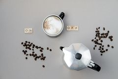 Cup of coffee switching on, grains and coffee pot on grey backgr. Ound. Top view, flat lay Royalty Free Stock Images