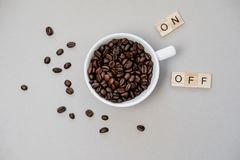 Cup of coffee switching on grey background. Top view, flat lay.  Royalty Free Stock Photography