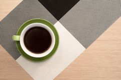 Cup of coffee on the table background and tablecloth. Green cup of coffee on the background of the pink wood table and black and white tablecloth. View from top Royalty Free Stock Photos