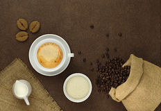 Cup of coffee on the table with beans, sugar and milk Royalty Free Stock Photos