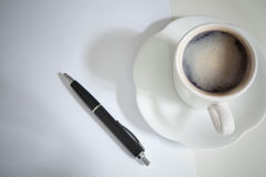 Cup of coffee on table with black pen on breaking Royalty Free Stock Images