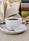 A cup of coffee on a table among books Royalty Free Stock Image