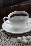 Cup of coffee on table with books Stock Images