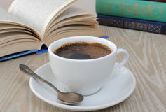 A cup of coffee on a table among books Stock Images
